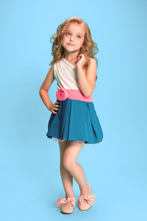 Full length of beautiful little girl in dress standing and posing over blue background Reklamní fotografie - 83551386