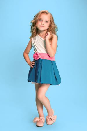 Volledige lengte van mooi meisje in kleding die en zich over blauwe achtergrond bevinden stellen Stockfoto - 83551386