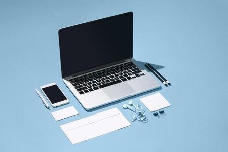 El portátil, bolígrafos, teléfono, nota con pantalla en blanco sobre la mesa Foto de archivo - 83551568