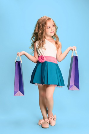 The cute little caucasian brunette girl in dress holding shopping bags Фото со стока