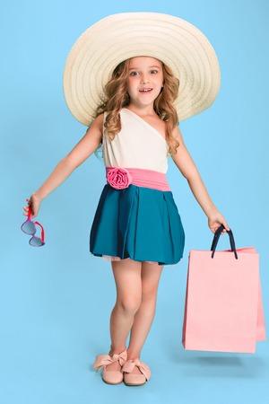 The cute little caucasian brunette girl in dress holding shopping bags Stock Photo
