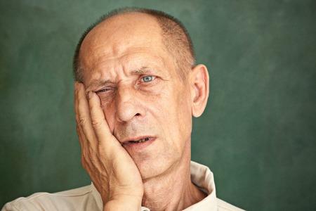 Besorgter, reifer Mann, der seinen Kopf berührt Standard-Bild - 83703936
