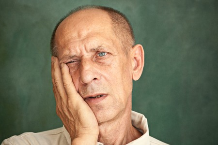 Worried mature man touching his head.