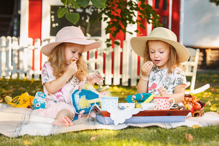 Two little girls sitting on green grass Stock Photo