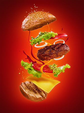 The hamburger with flying ingredients on red background