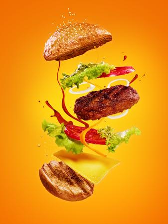 The hamburger with flying ingredients on orange background