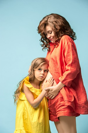 Pregnant mother with teen daughter. Family studio portrait over blue background