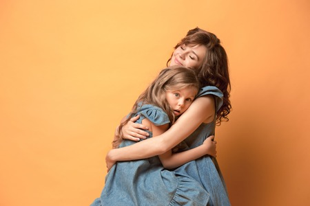 Pregnant mother with teen daughter. Family studio portrait over brown background