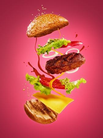 De hamburger met vliegende ingrediënten op roze achtergrond