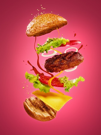 The hamburger with flying ingredients on rose background