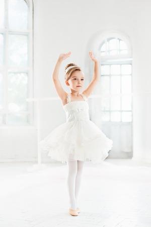 Pequena bailarina em um tutu. Adorável criança dançando ballet clássico em um estúdio branco. Foto de archivo - 84321626