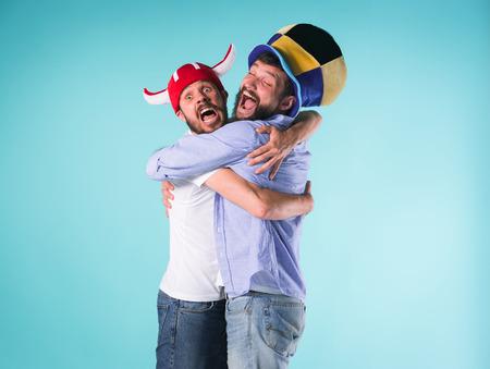 Dos amigos excitados masculinos celebran los deportes que se sientan Foto de archivo - 84756415