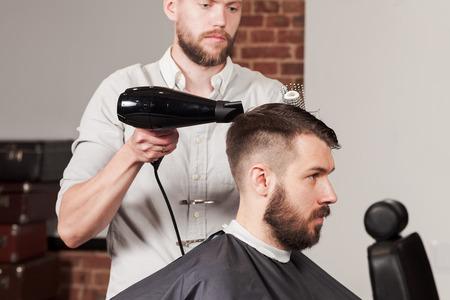 Junges stattlicher Barbier Herstellung des Haarschnitts von attraktiven Mann in Friseurläden Standard-Bild