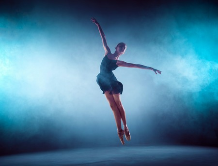 Beautiful young ballet dancer jumping on a lilac background. Stock Photo