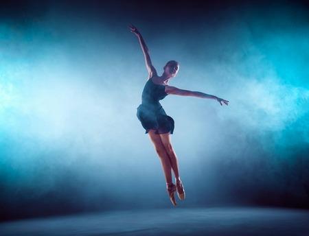 Mooie jonge balletdanser springen op een lila achtergrond.