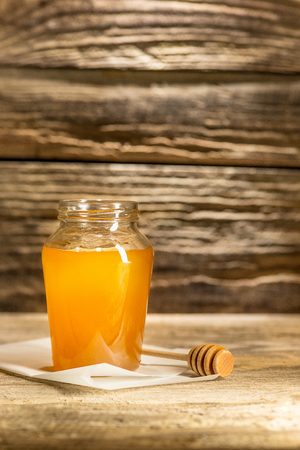 The bowl with honey on wooden table.The bank of honey stay near wooden spoon