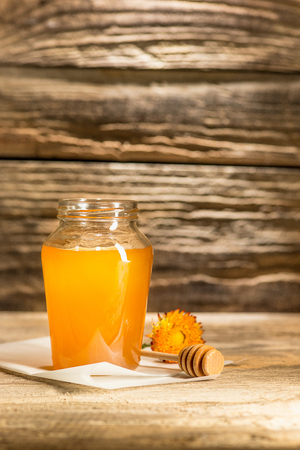 dulcet: The bowl with honey on wooden table.The bank of honey stay near wooden spoon