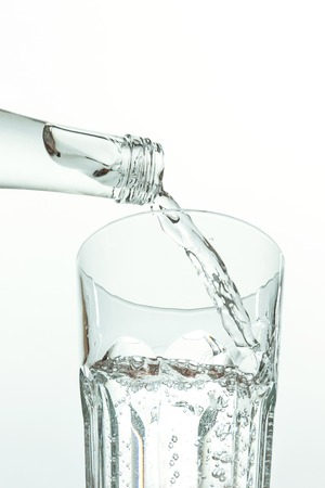 Pouring water from bottle into glass on white background Stok Fotoğraf - 86491657