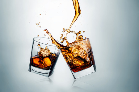 Two whiskey glasses clinking together on gray