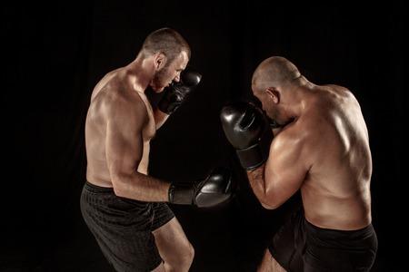 Two muscular men fighting, bodybuilders punching each other, training in martial arts, boxing, jiu jitsu