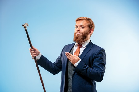 Tattooed bearded man in a suit holding cane.