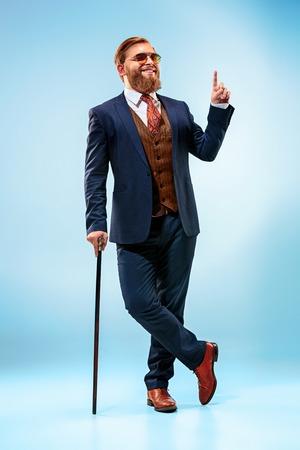 Der barsche Mann in einem Anzug, der Stock hält. Standard-Bild - 86094120