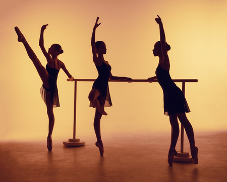 Composition from silhouettes of three young dancers in ballet poses on a orange background.