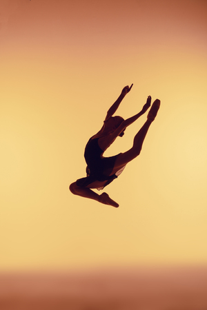 Beautiful young ballet dancer jumping on a orange background.