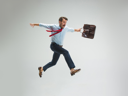 Zakenman die met een aktentas loopt, die op grijze achtergrond wordt geïsoleerd Stockfoto