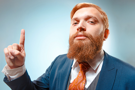 Portrait of a business man isolated on blue background.