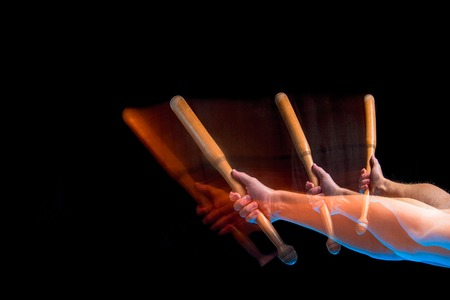 The arm with wooden baseball bat on black background