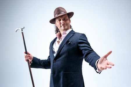 The mature man in a suit and hat holding cane. Stock Photo