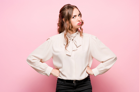 The serious frustrated young beautiful business woman on pink background Reklamní fotografie - 87047640