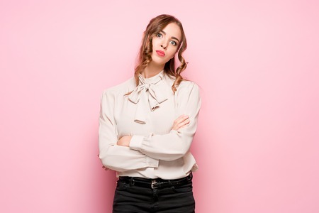 The serious frustrated young beautiful business woman on pink background