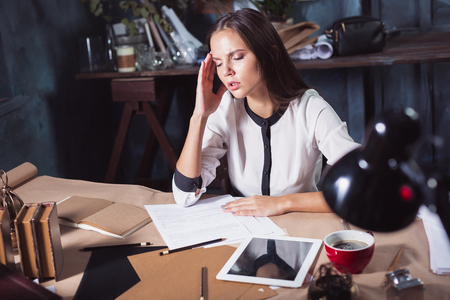 tired: Young frustrated woman working at office desk in front of laptop