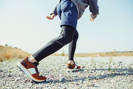 Sporten. Mensenloper die openlucht in toneelaard sprint. Fit gespierde mannelijke atleet training trail loopt voor marathon lopen. Stockfoto