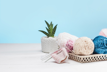 The balls of wool on white wooden background