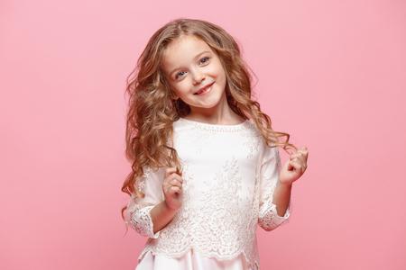 Het mooie meisje in jurk permanent en poseren op witte achtergrond