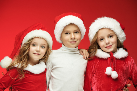 The happy boy and girls in santa claus hats with gift boxes at studio
