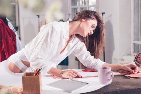 机の上に座ってスタジオでの作業のファッション ・ デザイナー