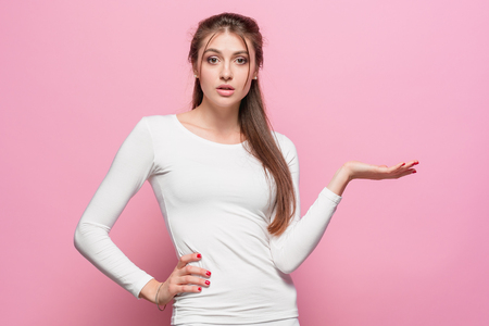 desilusion: The serious frustrated young beautiful business woman on pink background