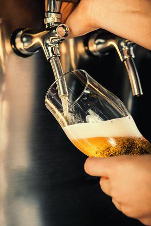 Mano del barman que vierte una cerveza de cerveza dorada grande en golpecito.