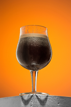brewery: glass of cold frothy dark beer on an old wooden table