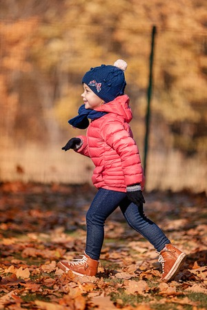 The little baby girl playing in autumn leaves Reklamní fotografie