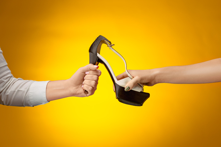 Brown woman shoe with female and male on hands Stock Photo