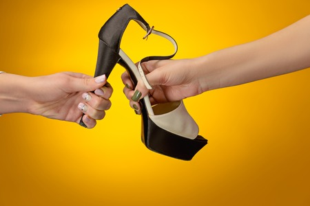 varnished: Brown woman shoe with female and male on hands Stock Photo