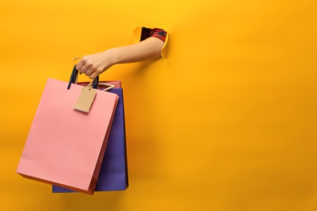 Female hand holding bright shopping bags Standard-Bild