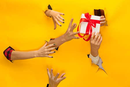 torn edge: close-up of female hand holding a present through a torn paper, isolated