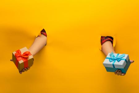 Close-up van vrouwelijke hand met een cadeautje door een gescheurd papier, geïsoleerd Stockfoto - 89005744