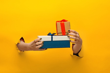 close-up van vrouwelijke hand met een cadeautje door een gescheurd papier, geïsoleerd